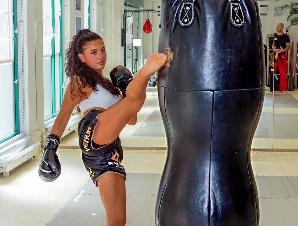 Junge Frau in Kickbox-Schule kickt gegen einen Boxsack.