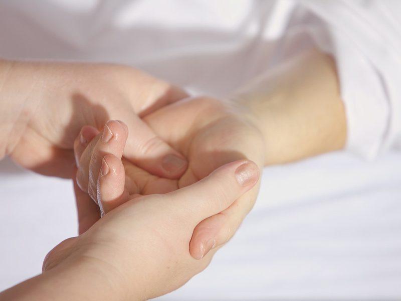 Zwei Hände massieren eine andere Hand als manuelle Therapie