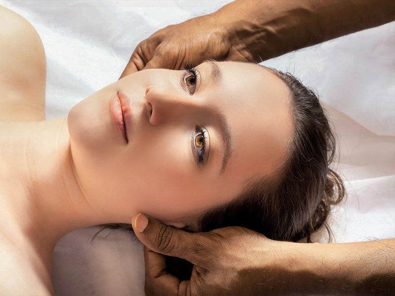 Zwei Hände behandeln eine Frau am Kopf oder Gesicht an den Lymphknoten